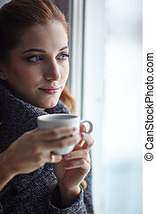 Young pretty woman in wool sweater with white coffee cup in...
