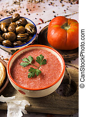 spanish gazpacho and escargots - a ceramic bowl with...