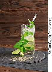 Cool mojito cocktail with rum, mint, ice cubes and lime in a highball glass on the wooden background. Alcoholic drink. Copy space.