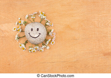 Smiley stone and daisies lying on a wooden surface.