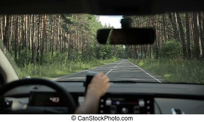 Woman driving empty country road through forest - Car riding...