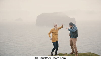 Young tourist man and woman standing at the edge of the mountain and dancing. Tourists having fun together.