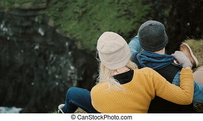 Back view of young couple sitting at the edge of cliff and resting. Tourist man and woman enjoying the beautiful view.