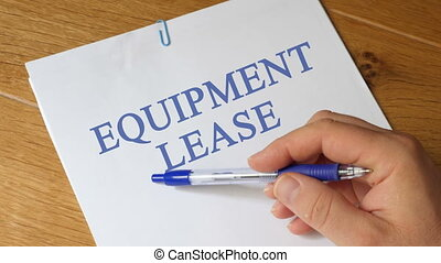 Equipment Lease Concept - Equipment Lease papers on a wooden...