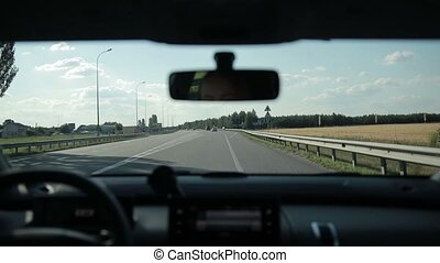 Driving car on freeway on summer day - Young woman driving...