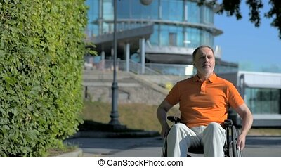 Serious senior man using wheelchair outdoors - Confident in...