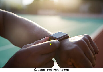Close up of a young african sportsman adjusting smartwatch...