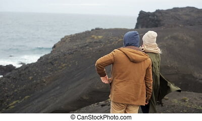 Young stylish couple standing on the cliff and enjoying the view of the sea. Man pointing on something and woman looking