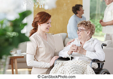 Older woman sits on wheelchair next to nurse and is holding...