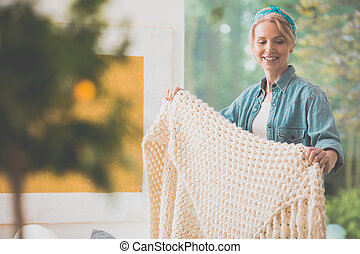 Woman is arranging white coverlet during domestic duties in...
