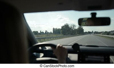 Car riding on highway in sunlight - Woman driving car on...