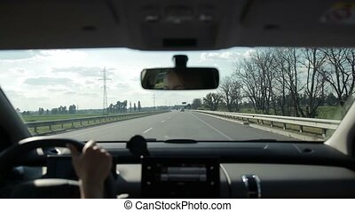 Car on asphalt motorway in countryside - Young female driver...