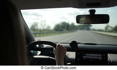 Car on empty highway in sunlight - Woman driving car on...