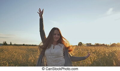 A young girl jumps from happiness at sunset in the evening sun. Against a background of wheat field.