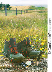 Hiking boots with knife and compass on log in field - Hiking...