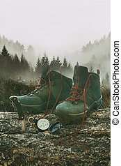 Hiking boots with knife and compass on tree log with...