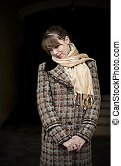 Shy young woman in the brown coat