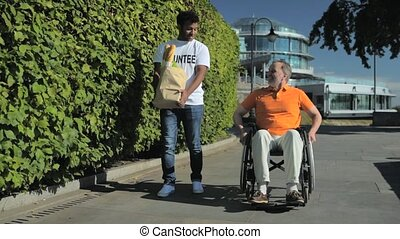 Positive volunteer helping wheelchaired man with carring...