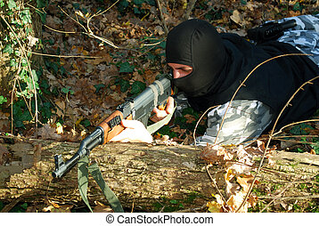 terrorist in camouflage aiming with his rifle outdoor in...