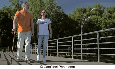 Delighted senior man walking with a cheerful female...