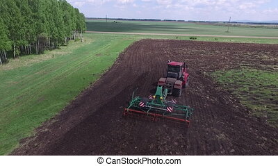 Tractor sowing seeds in the farm field on sunny autumn's day,