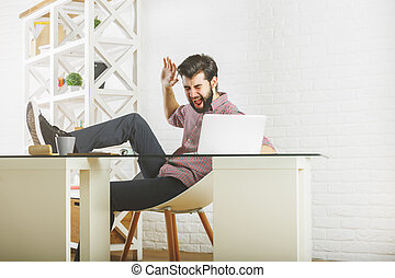 Furious man breaking laptop - Furious young man at workplace...