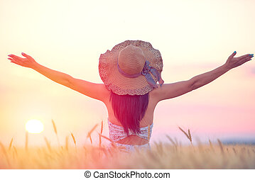 Woman feeling free, happy and loved in a beautiful natural setting at sunset