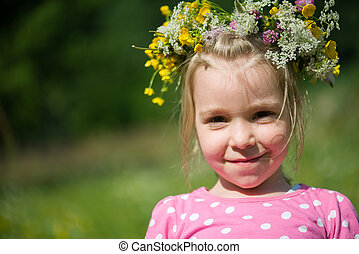 Portrait of a blonde little girl with a wreath of flowers on her head