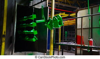 Drying rail in the factory with hanging green details of Agricultural machinery