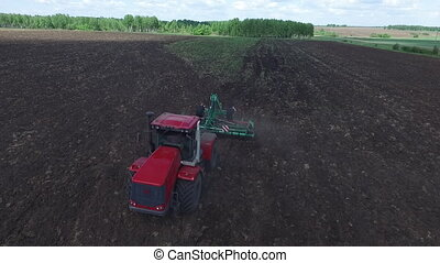 Aerial drone shot of a farmer in tractor seeding, sowing...
