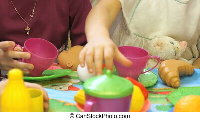 Little girls playing with plastic tableware. Close up