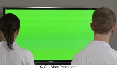 Doctors looking to TV with green screen. Scientists looking to screen with chromakey