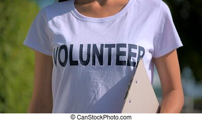 Pleasant female volunteer standing with a folder in hands -...