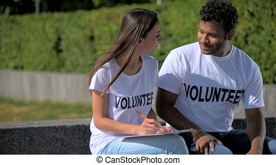 Positive international volunteers sitting in the park -...