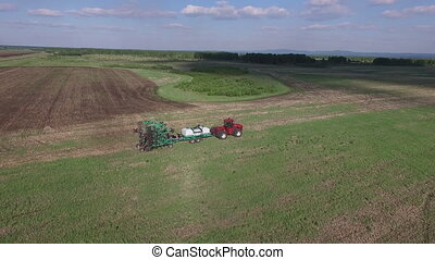 Farmer plowing a field with a tractor air view dron