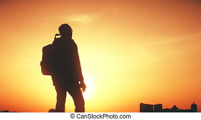 Silhouette of a man with a backpack against bright sky...