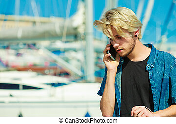 Blonde man talking on mobile phone