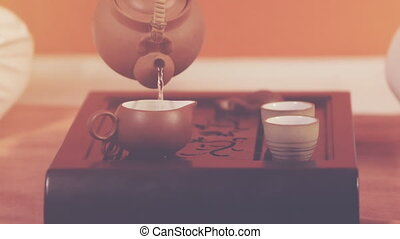 Tea ceremony. Orange toning - Tea ceremony. A man pours...
