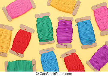 Spool of threads on yellow background