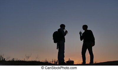 Man and boy drinking bottle of water on travel silhouette...