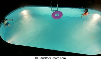 Boy and girl bathe in the pool at night. Children kids...