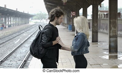Romantic couple kissing and hugging in train station on...