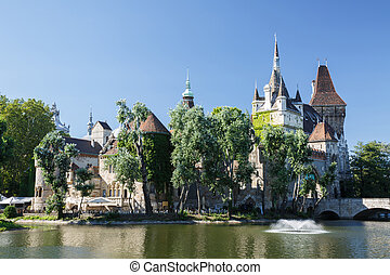 beautiful view of the Vajdahunyad Castle surrounded by trees...