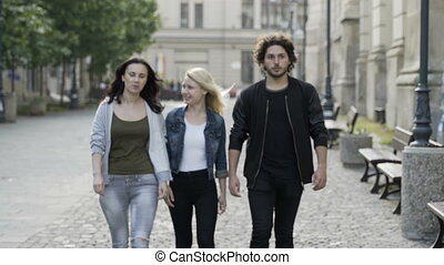 Group of three friends walking on street expressing surprise...