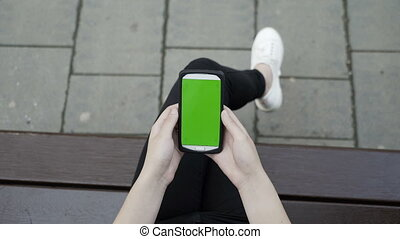 Closeup of woman sitting on a bench in a park holding a smartphone with green screen chroma key