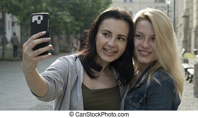 Closeup of best girls friends standing together for a selfie...