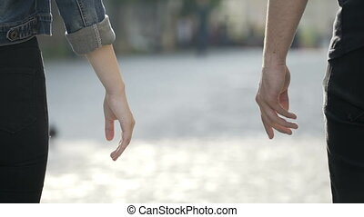 Closeup of man and woman touching hands and enjoying a walk together in a park