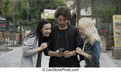 Cheerful group of teenage friends using smartphone for entertainment in urban environment having fun