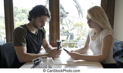Teen couple with relationship issues networking on social media using smartphones sitting at table in restaurant