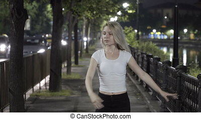 Young blonde girl dancing ballet on street at night...